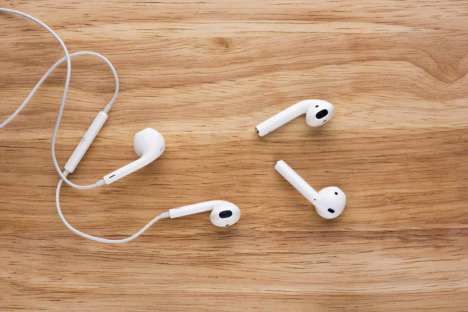 Airpods and Earpods are lying on a wooden surface