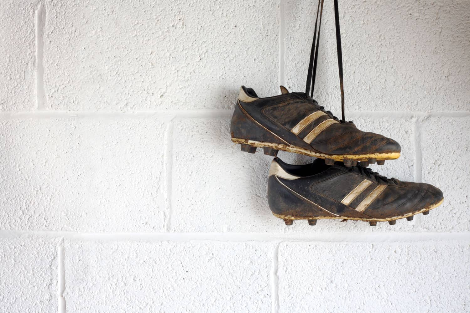 Dirty soccer cleats hanging on a concrete wall