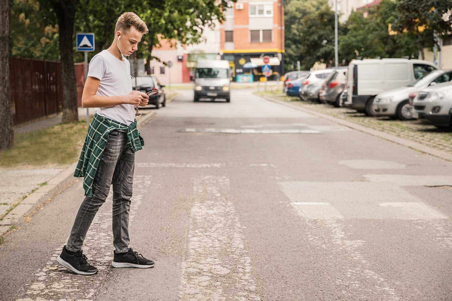 Kid crossing the street at a pedestrian crossing and listening to music on his cellphone