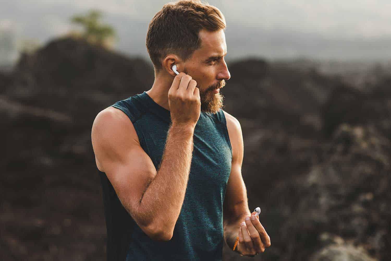 Man using wireless earphones air pods on running outdoors