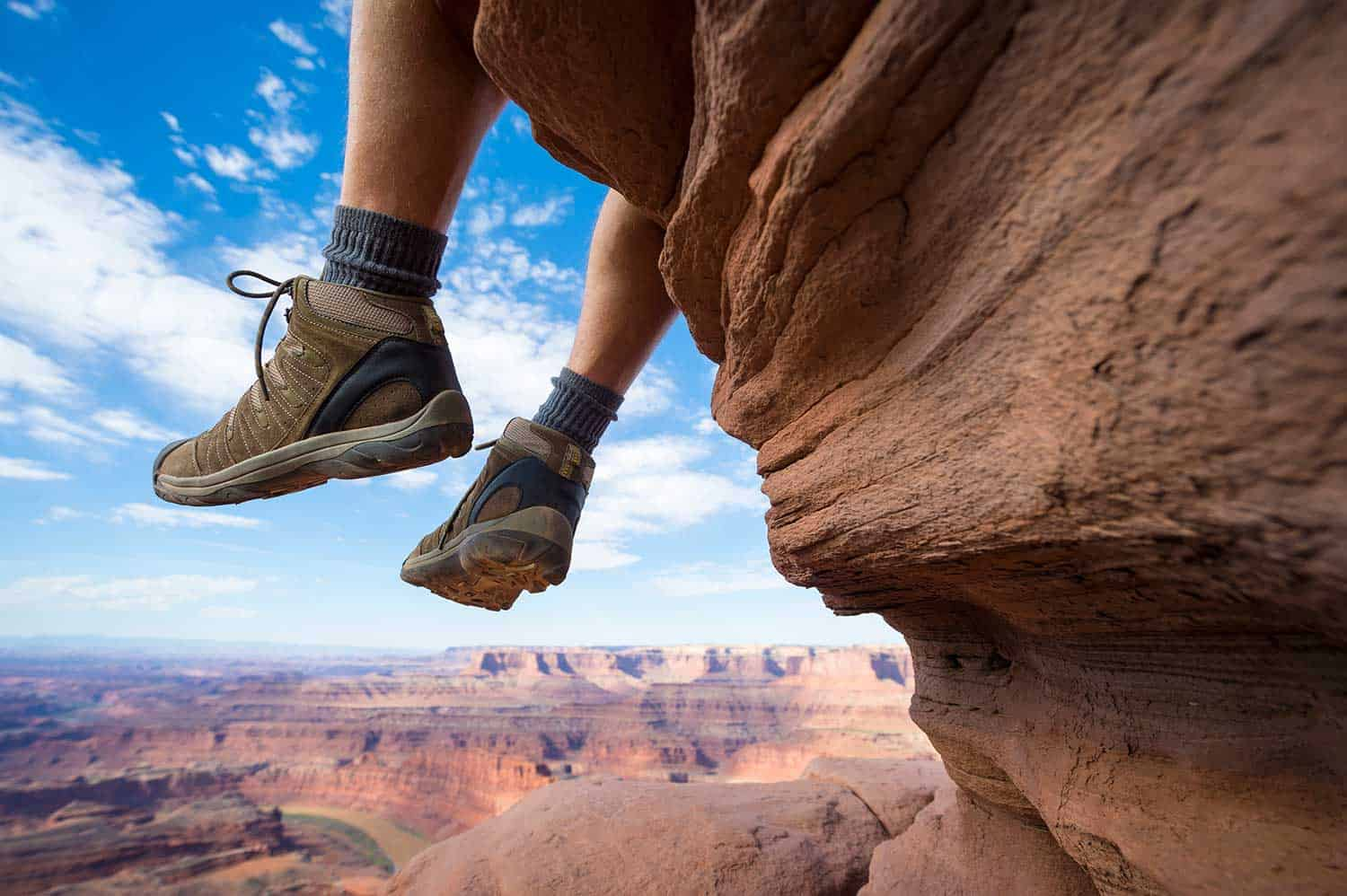 Portrait of the boots of a hiker hanging outdoors above dramatic canyon landscape