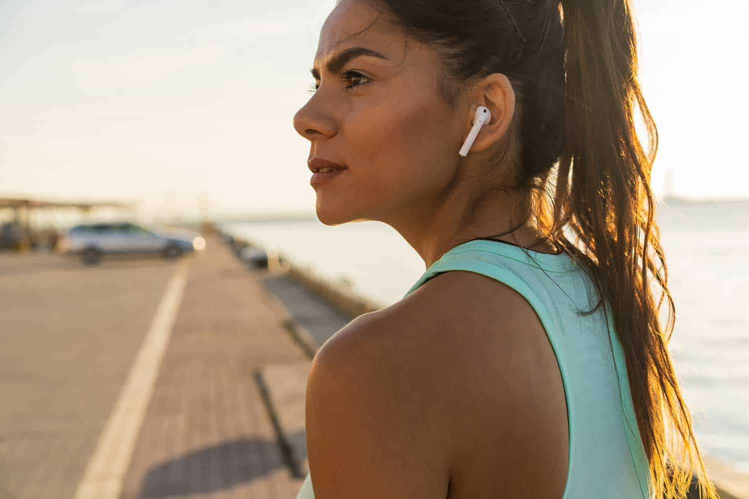Tired fitness woman sweating taking a break listening to music on phone after difficult training