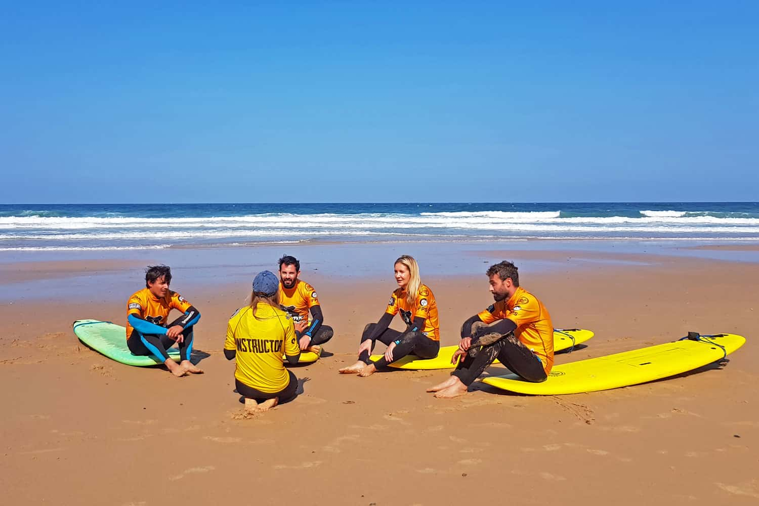 Young men and woman listening to their mentor about surfing lessons
