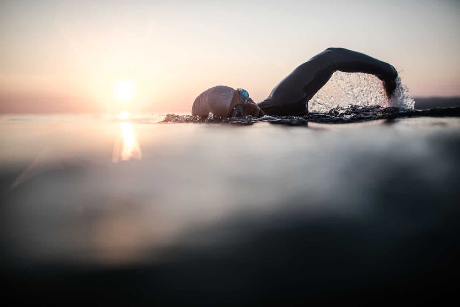 A detailed photo of a man swimming on open waters competing on an Ironman triathlon competition