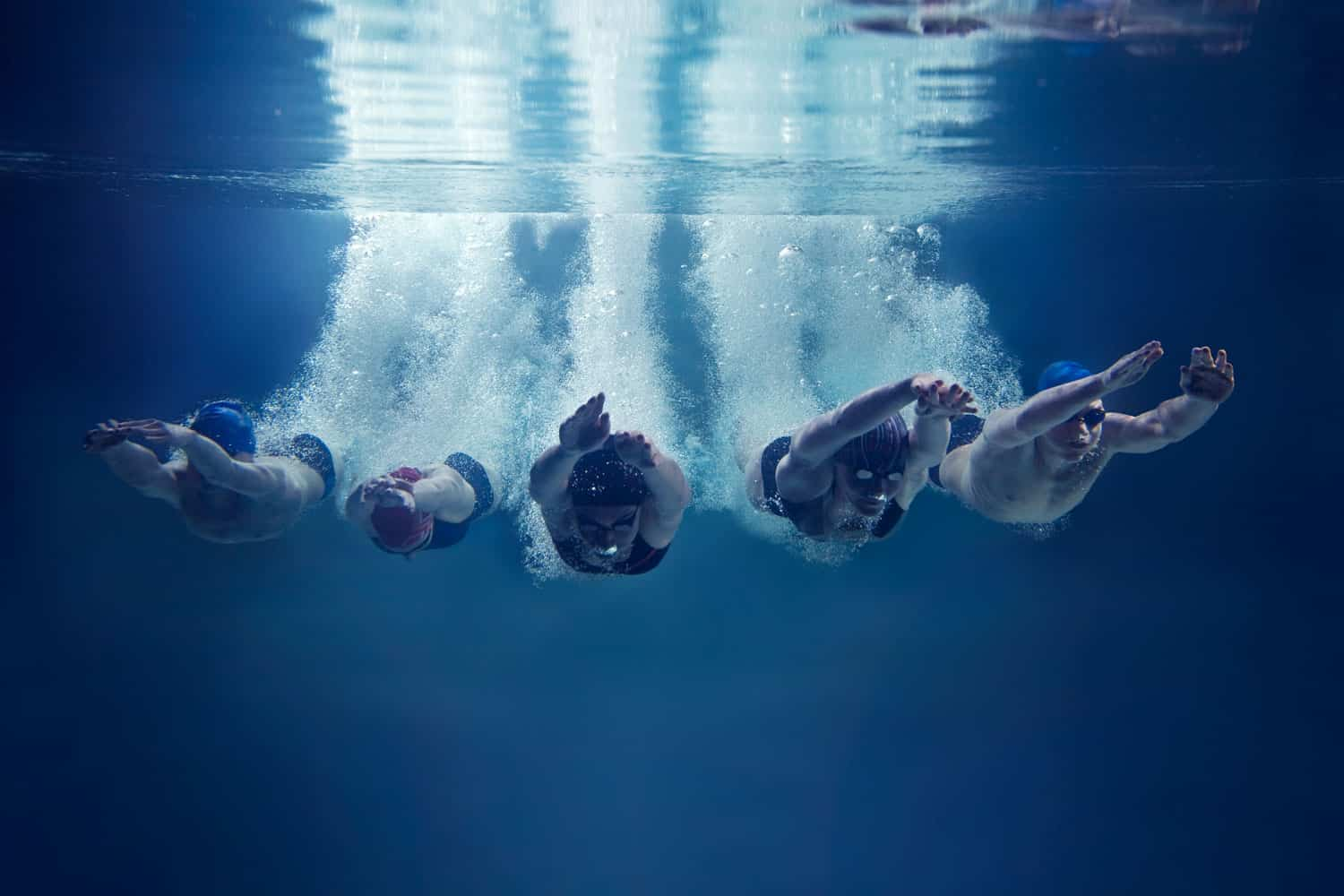 A group of swimmers diving together on an Olympic swimming pool