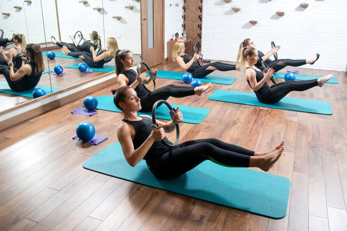 A group of women doing Pilates work holding exercising rings while sitting on their yoga mats