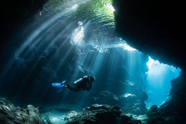 A lone scuba diver diving down a deep underwater cave