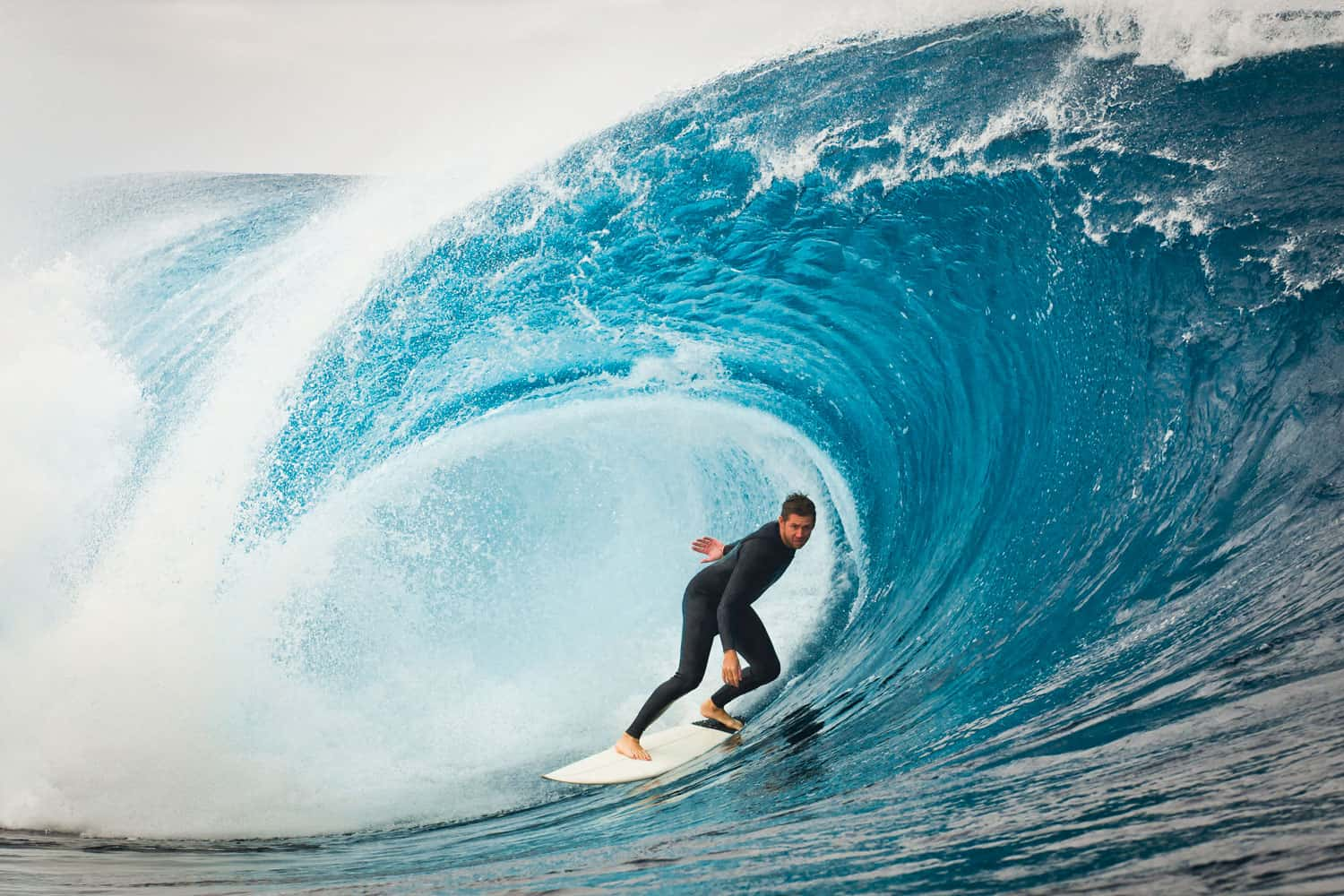 A man surfing a huge wave with his surfboard