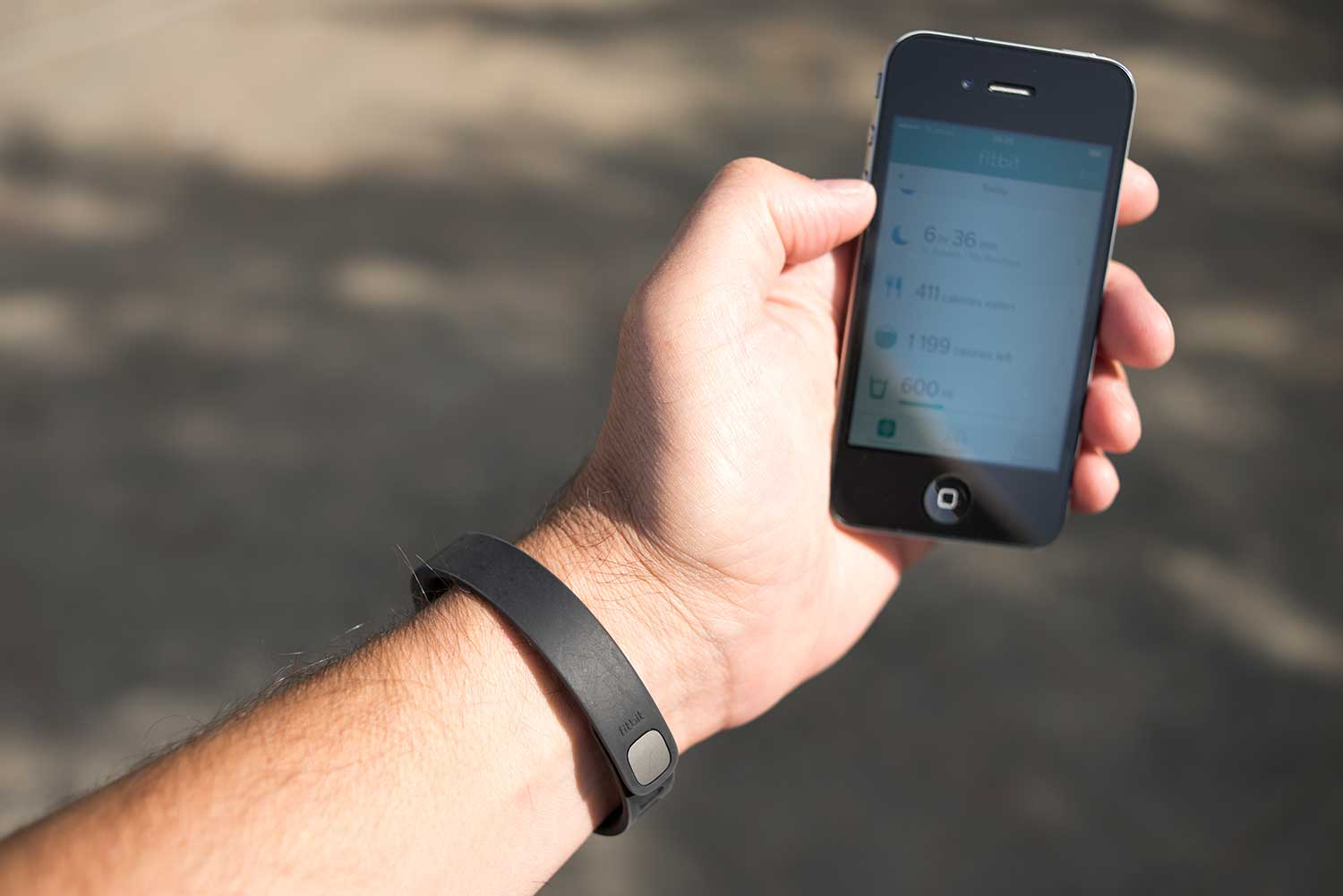 A man wearing a black Fitbit Flex activity tracking wristband uses the Fitbit application on an iPhone