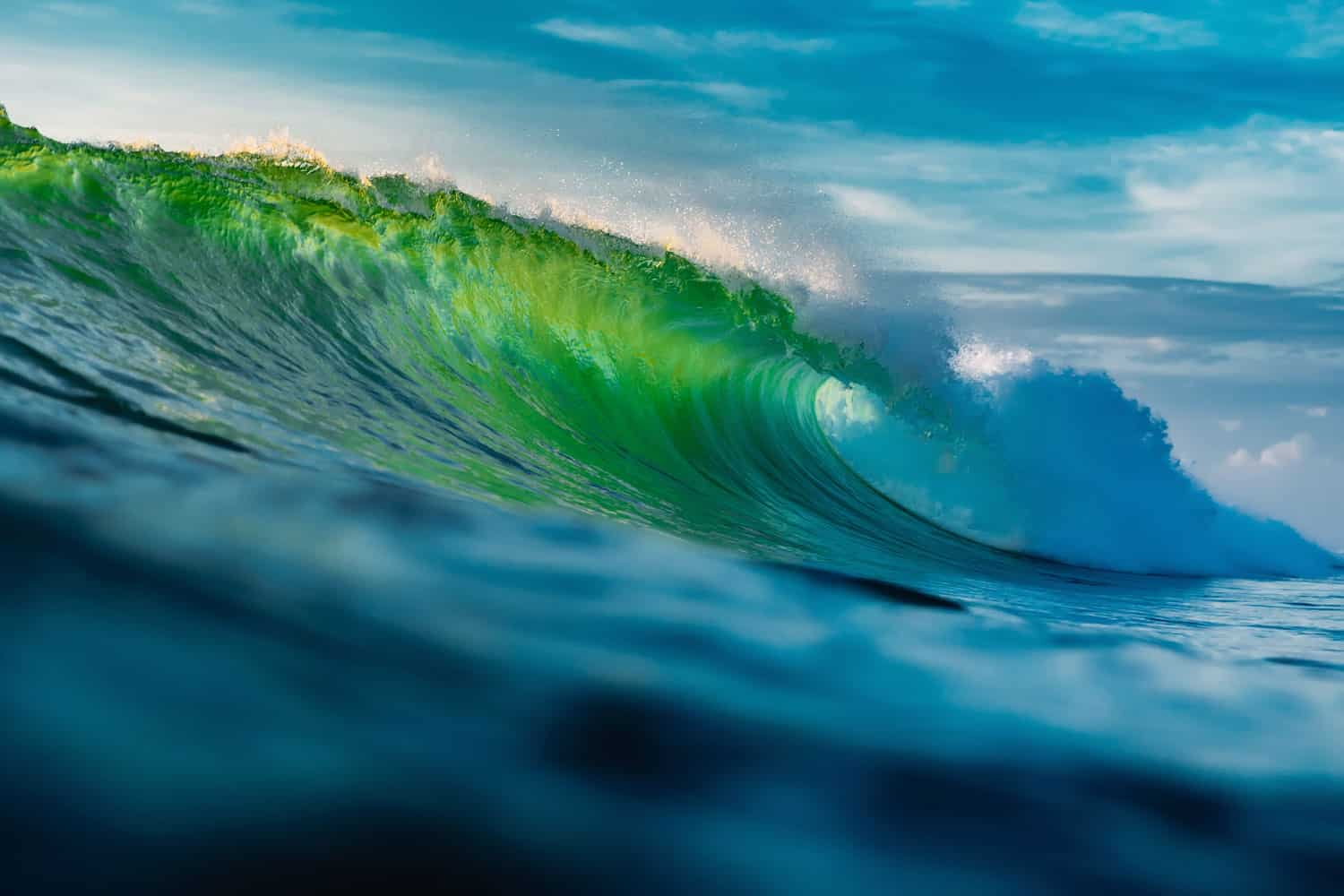 A perfect crest of a wave beaming green due to sunlight