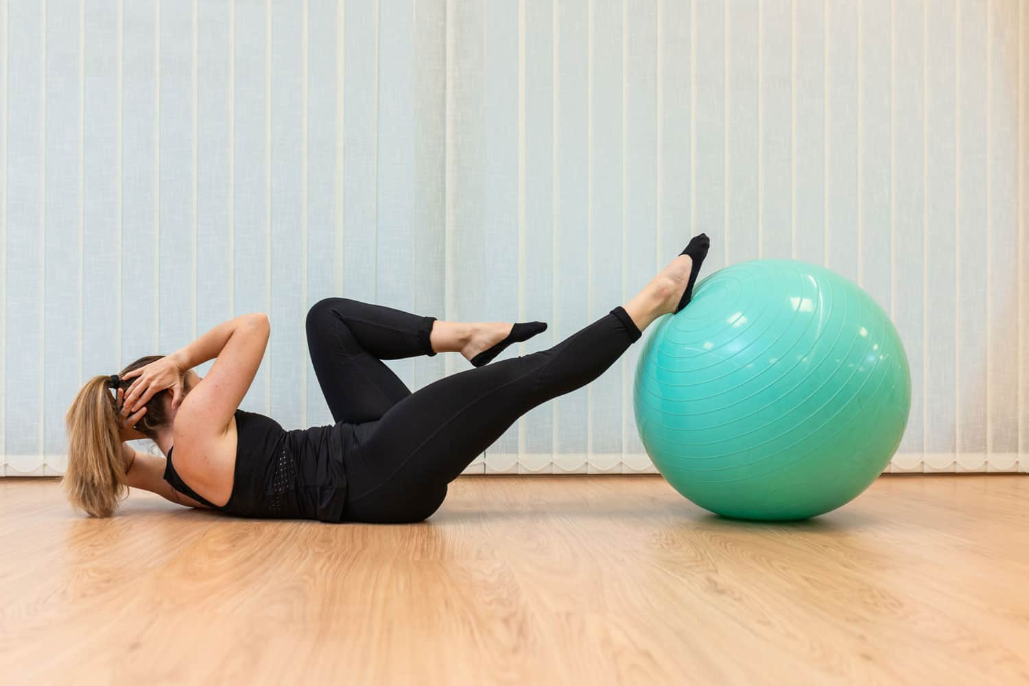 A woman doing criss cross on her fitball inside her living room
