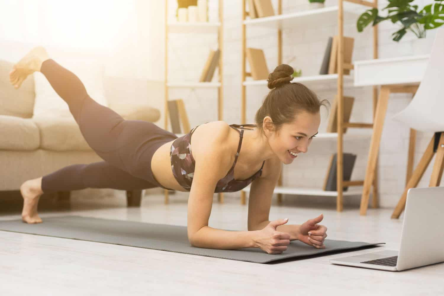 A woman doing planking on her yoga mat while watching a tutorial on her laptop