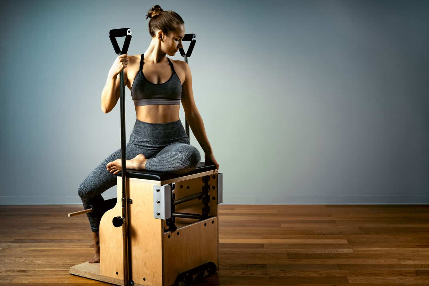 A woman sitting on a combo wunda pilates chair inside her gym