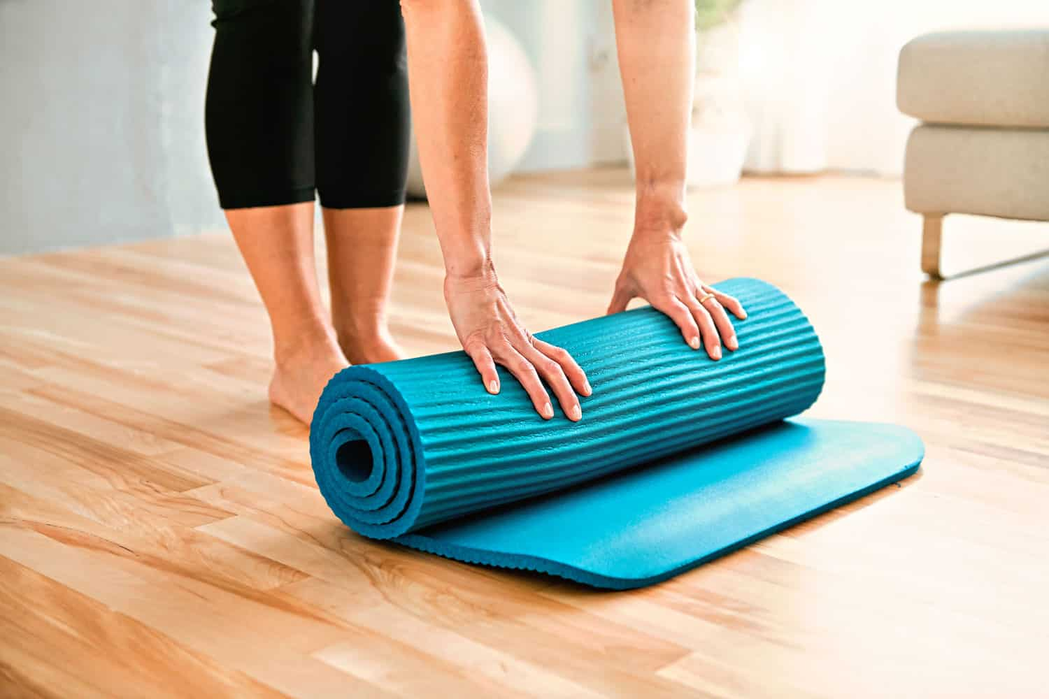 A woman unrolling her yoga mat on her living room before doing pilates
