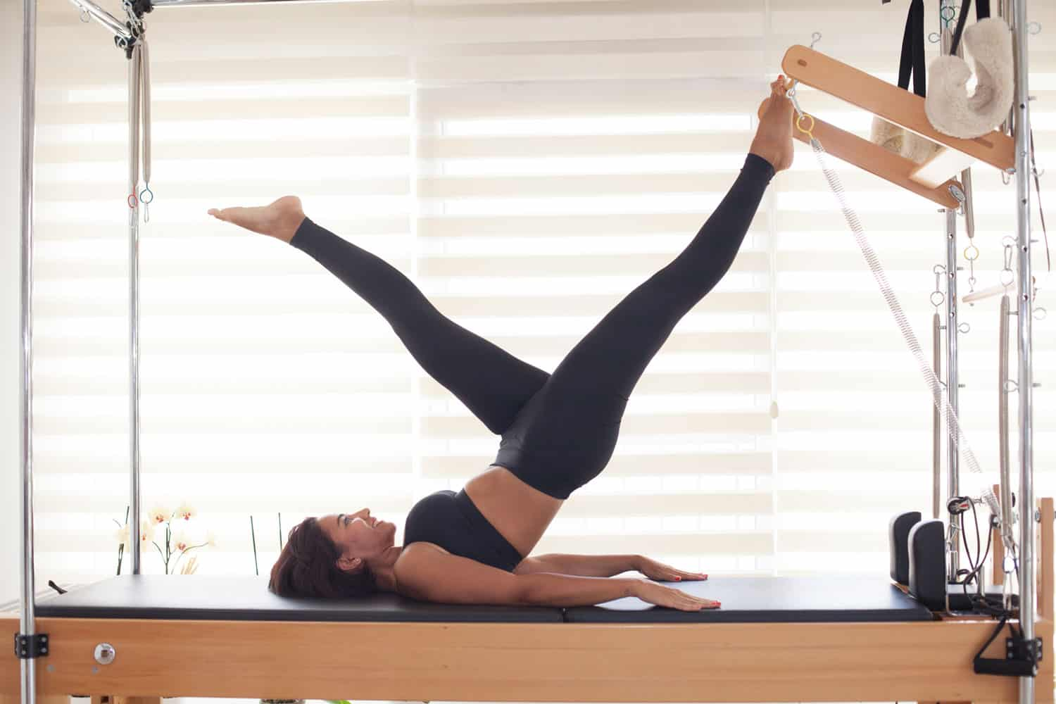 An aerobics instructor doing stretching exercise on her equipment