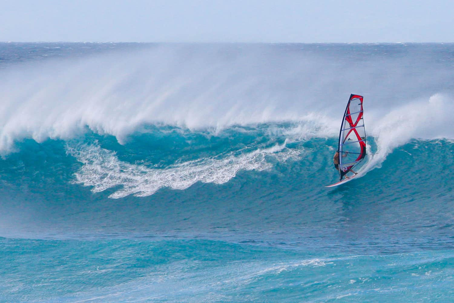 An extreme wind surfer riding a huge wave