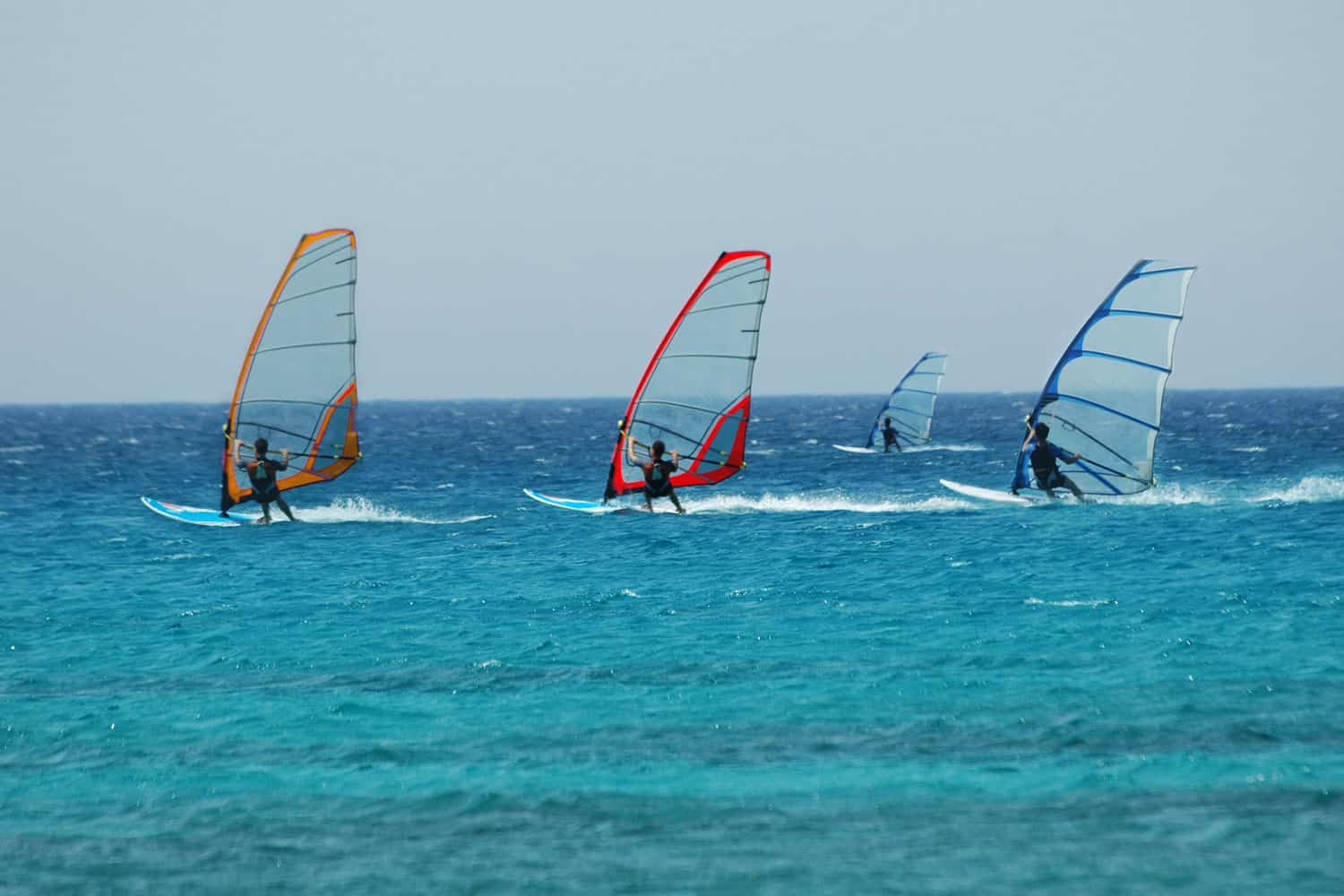 Four windsurfers riding their windsurfing boards out in the ocean