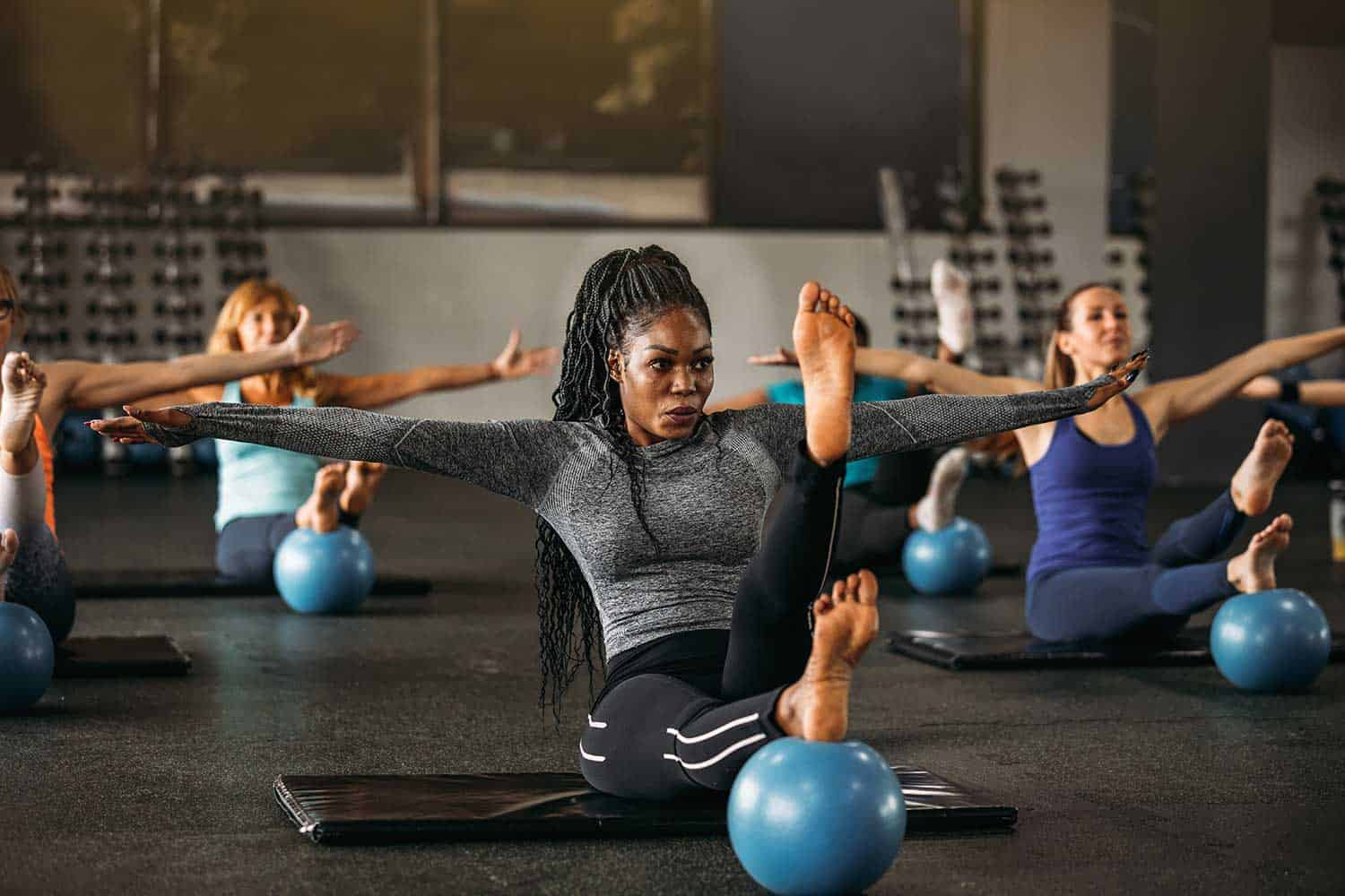 Group of women working balance exercise in the gym