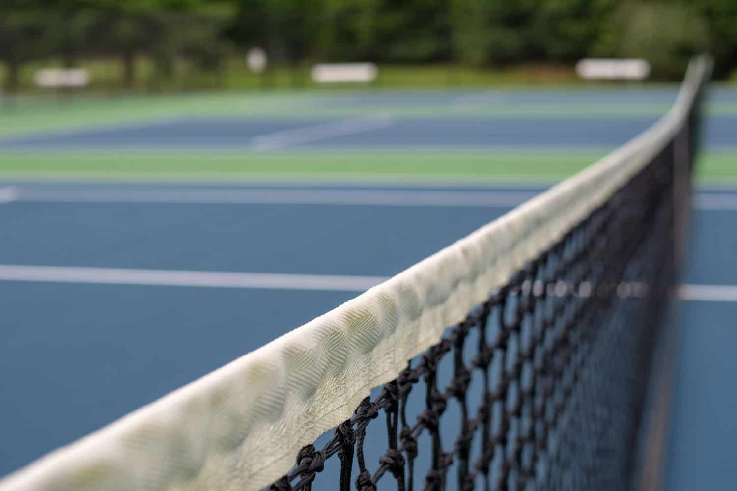 A close up of tennis court net with net in focus