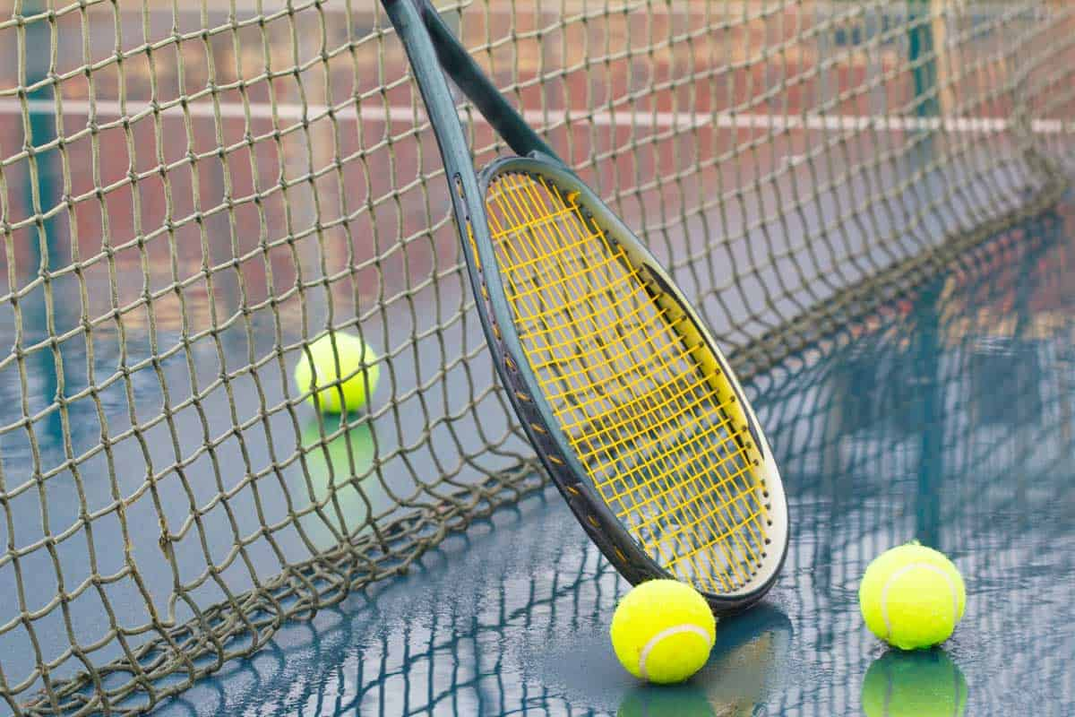 Racket leaning on net and wet tennis balls on court covered with rain, Can Tennis Rackets Get Wet?