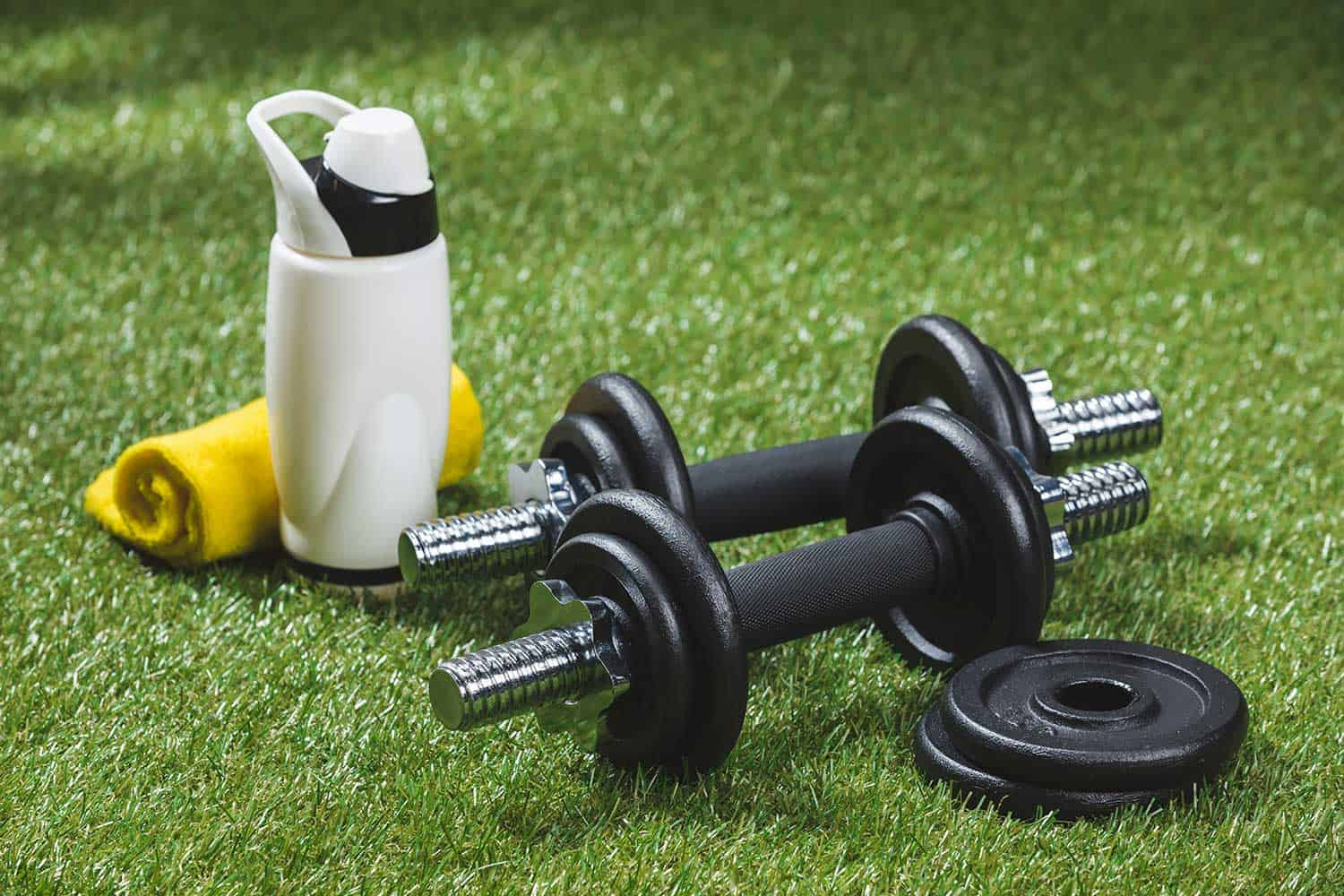 Dumbbells with weight plates and bottle of water with towel on grass