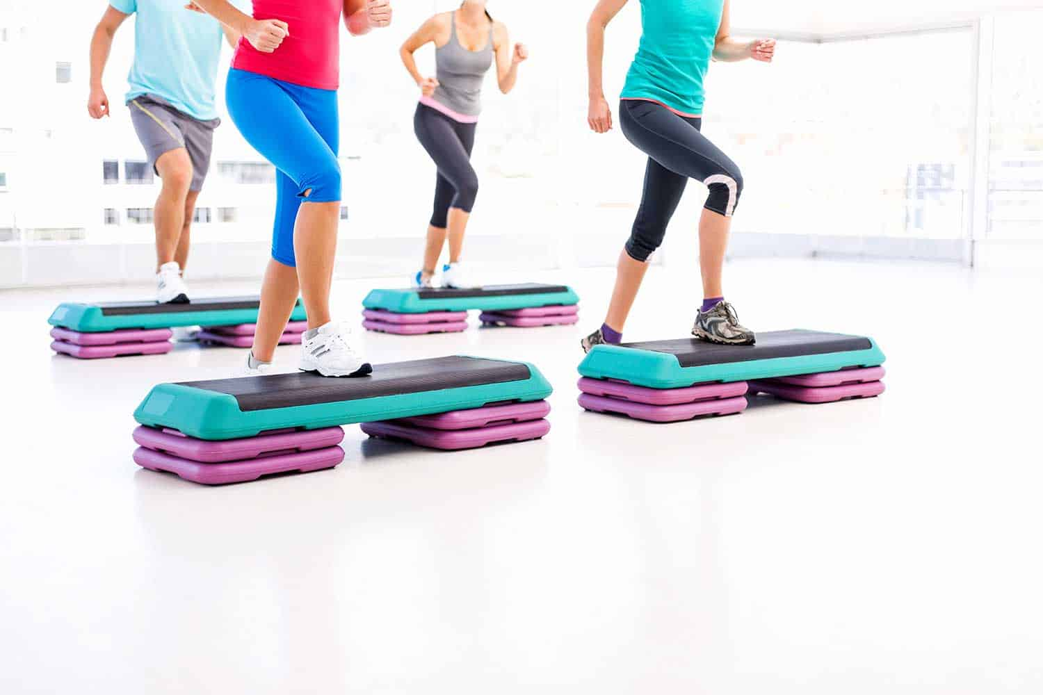 Low section of four friends doing aerobics using stair stepper in health club