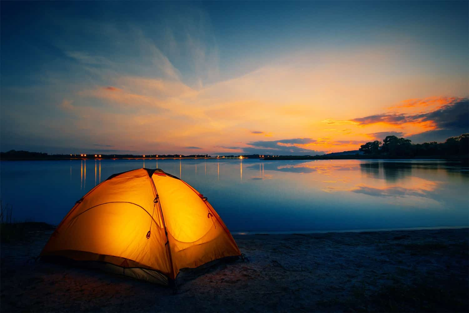 A four person orange colored tent set up near the lake