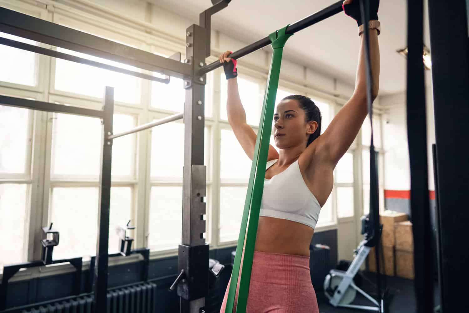 A woman doing a pull up workout inside the gym