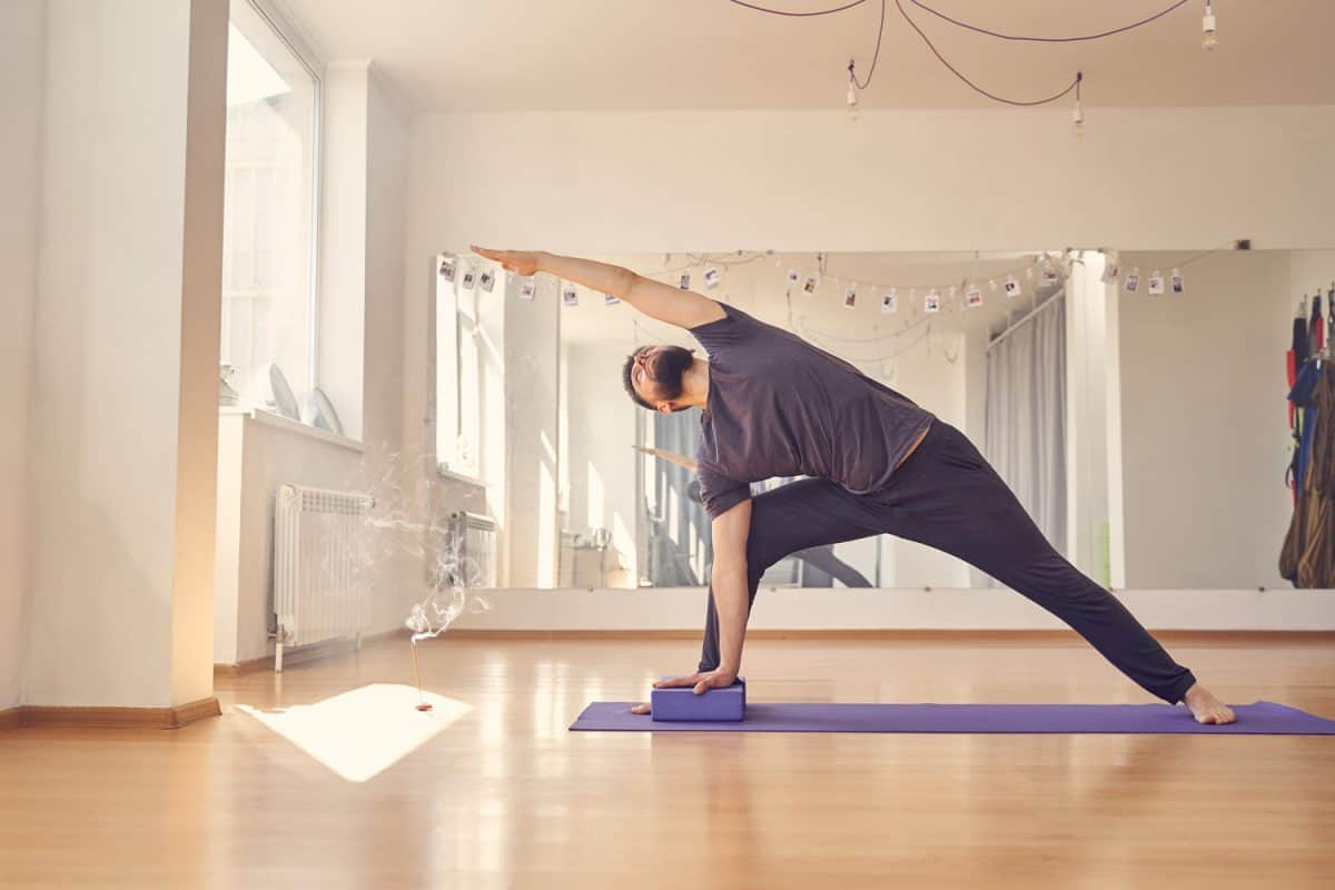 Athletic young man doing exercise with yoga blocks