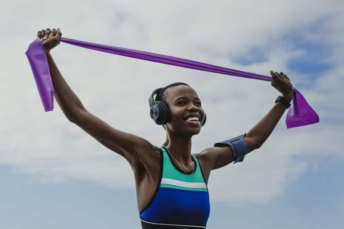 Happy woman in sportswear exercises with resistance band