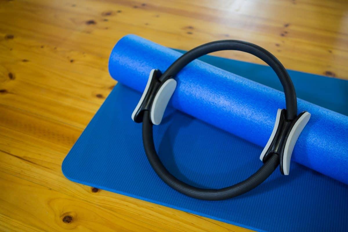 Pilates ring and exercise mat kept on wooden floor in fitness center