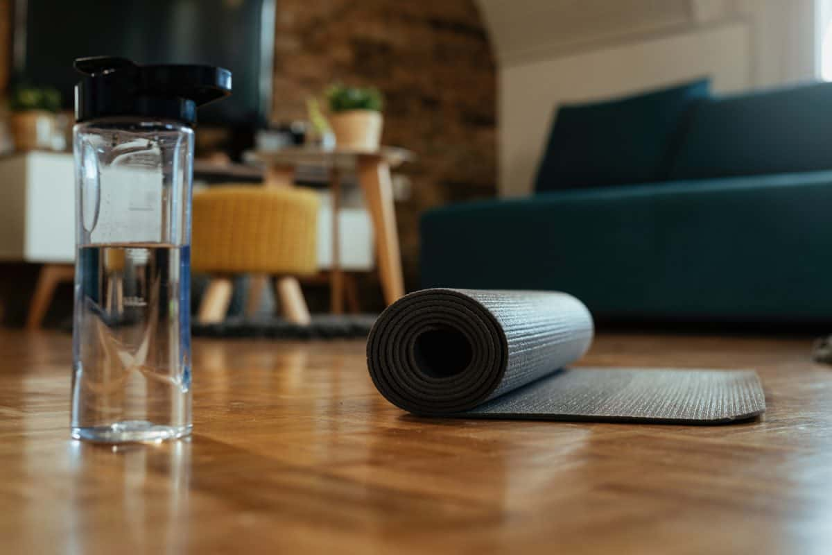 Rolled exercise mat and bottle of water on parquet floor.