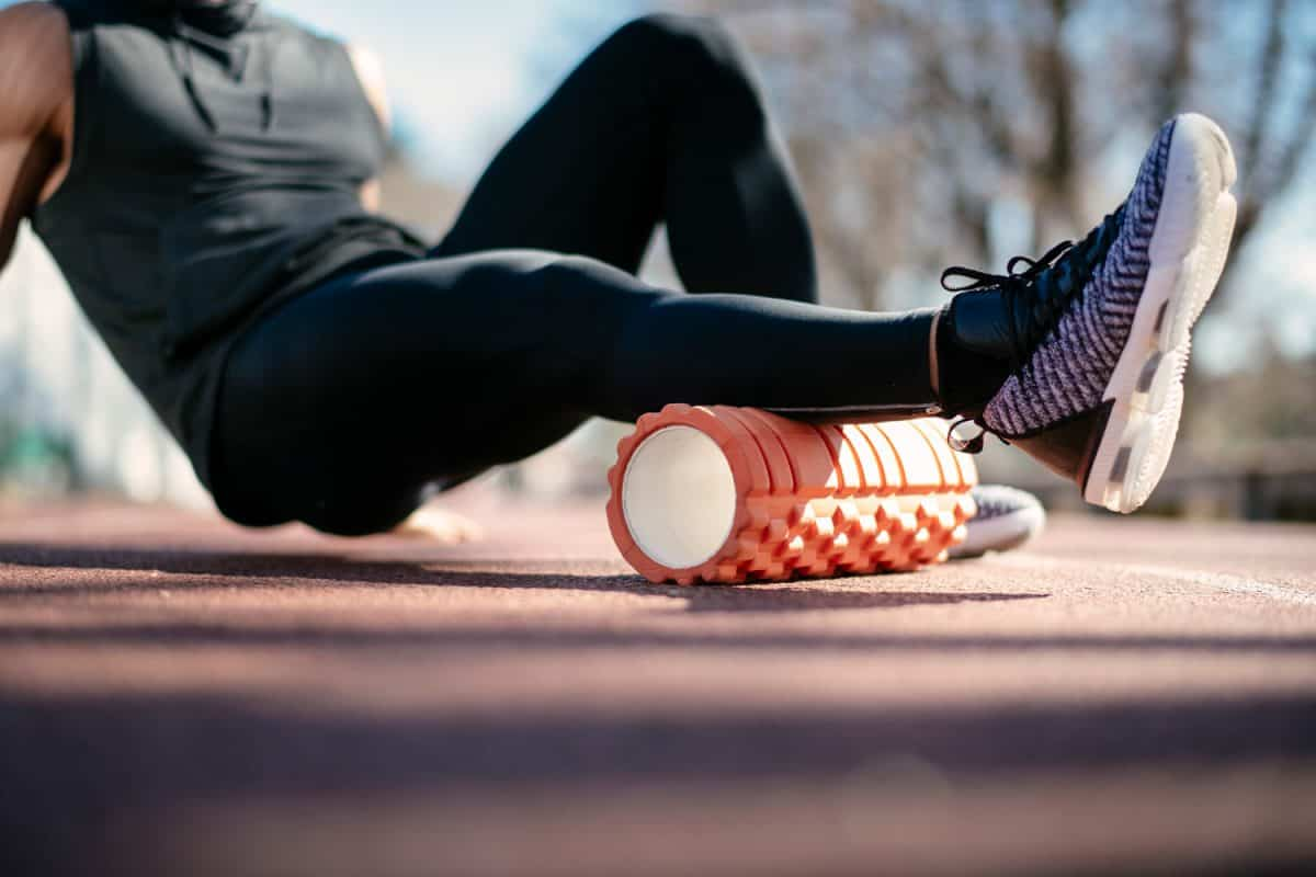 Young man stretching himself on a foam roller