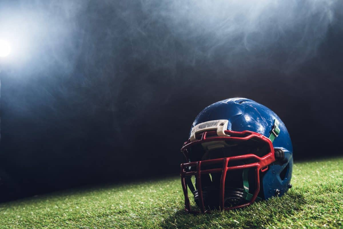 close-up shot of american football helmet on green grass with white smoke above,How Often Should A Football Helmet Be Reconditioned?