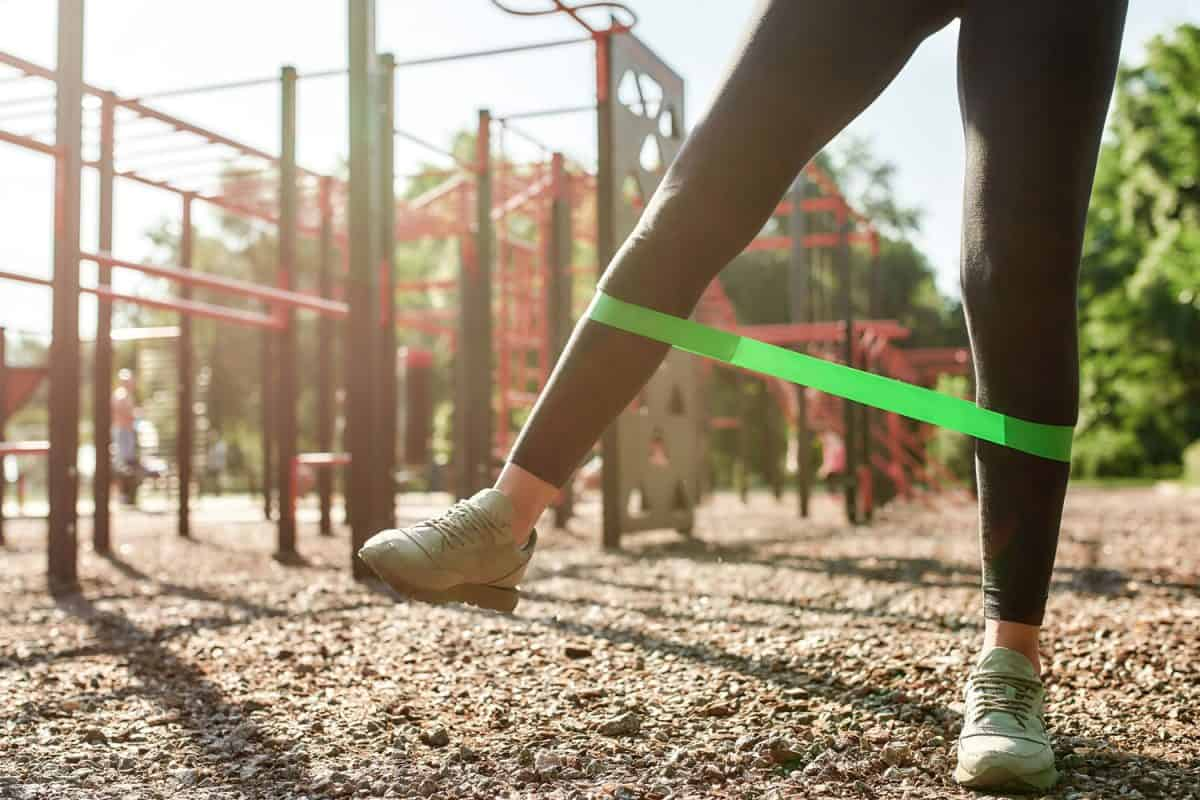 A teen on her leggings doing some resistance band workout on the playground