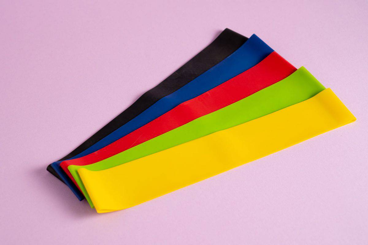 Different colors of resistance bands on a pink background