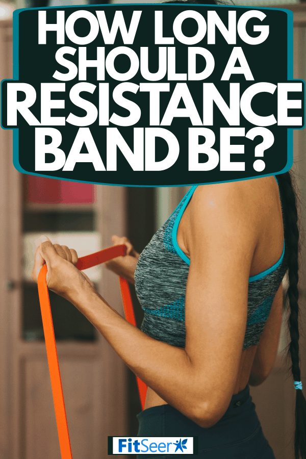 A woman holding an orange colored resistance band to use on her workout, How Long Should A Resistance Band Be?