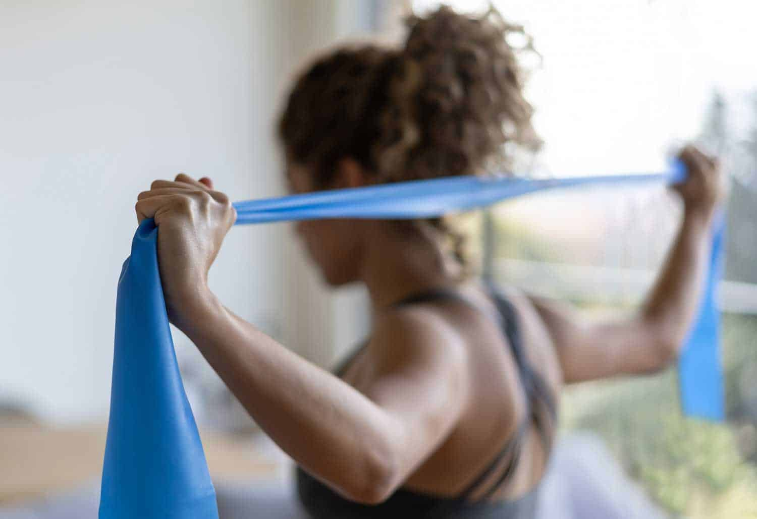 Strong woman exercising at home during the quarantine using resistance bands