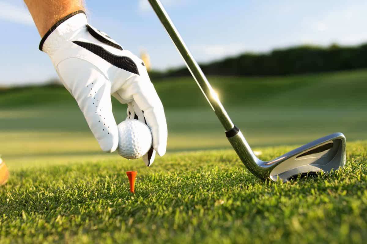 A golfer putting a golf ball on the pin