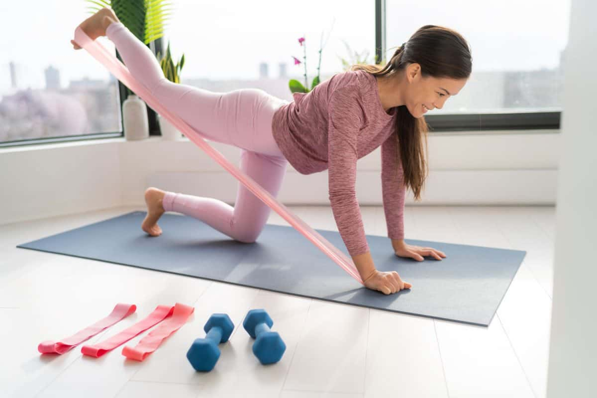 A woman doing a resistance band workout inside her living room