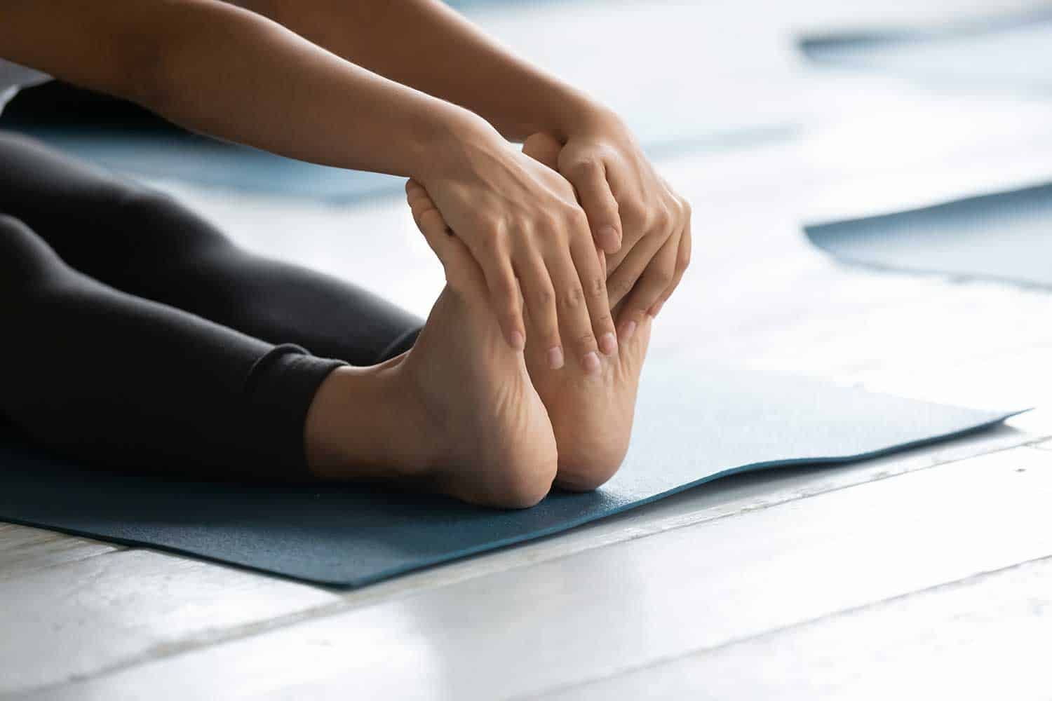 Close up of a young fit woman stretching on fitness mat
