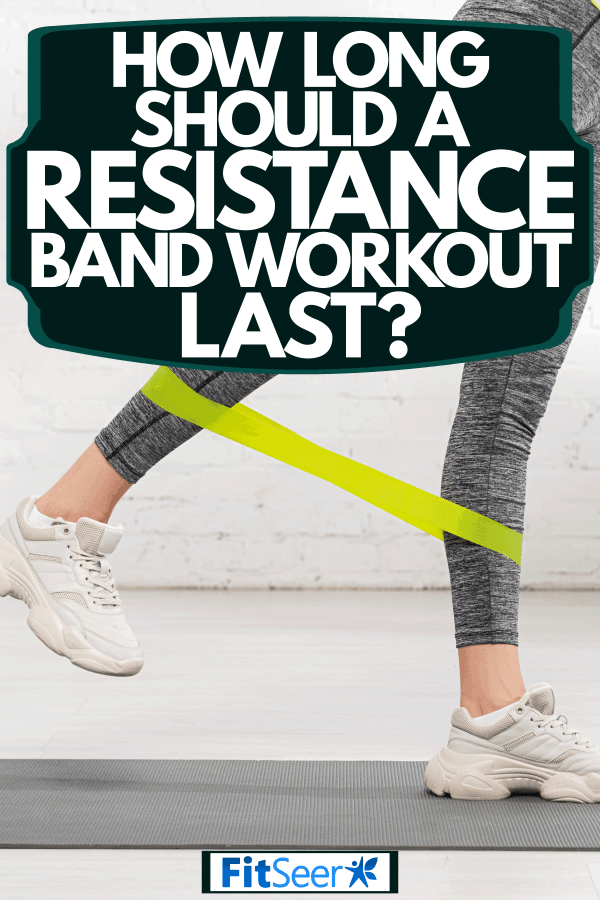 A woman wearing grey leggings and doing a resistance band workout, How Long Should A Resistance Band Workout Last?