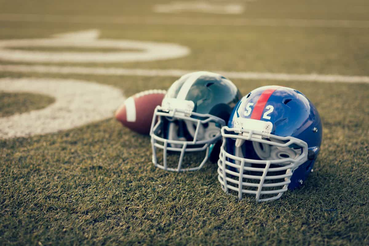 Two football helmets and a football left on the middle of the field