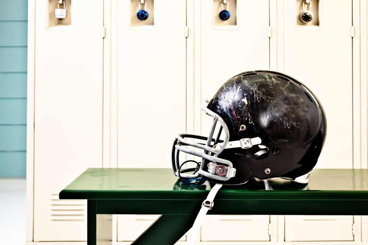 A cracked and used football helmet inside the locker room