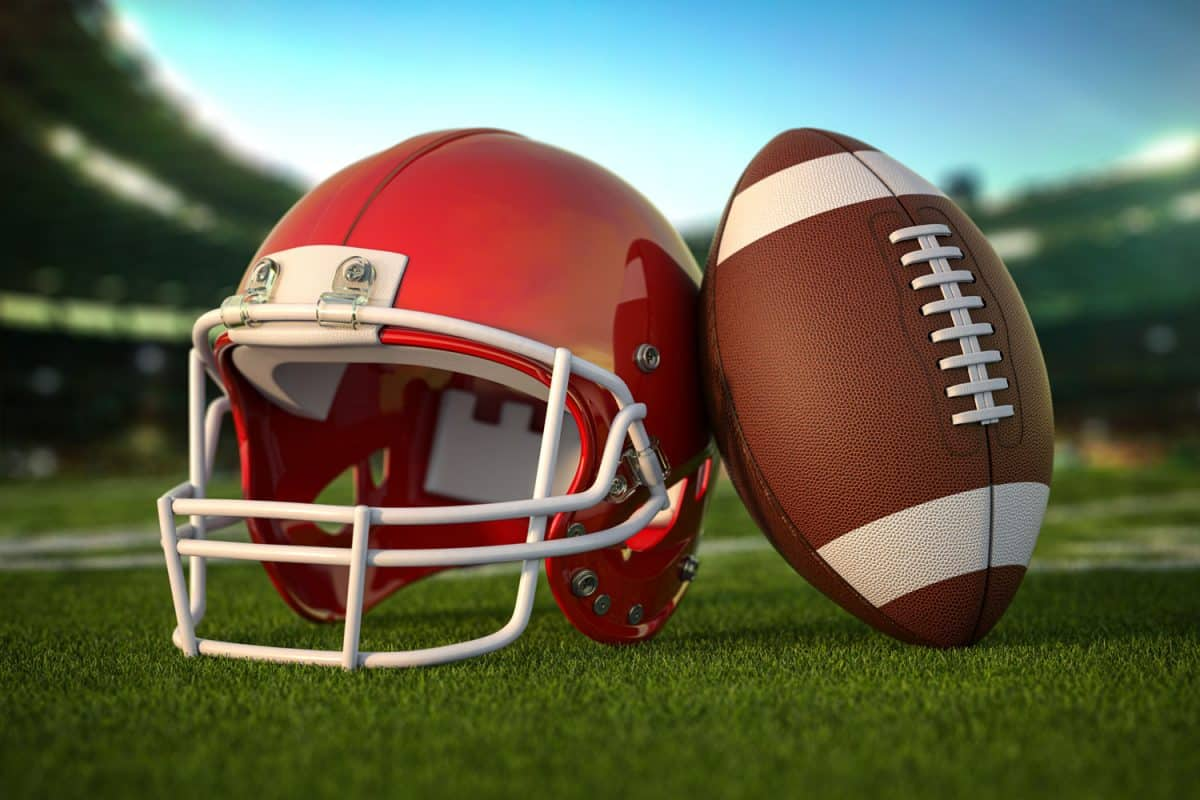 A red football helmet next to a football left on the field