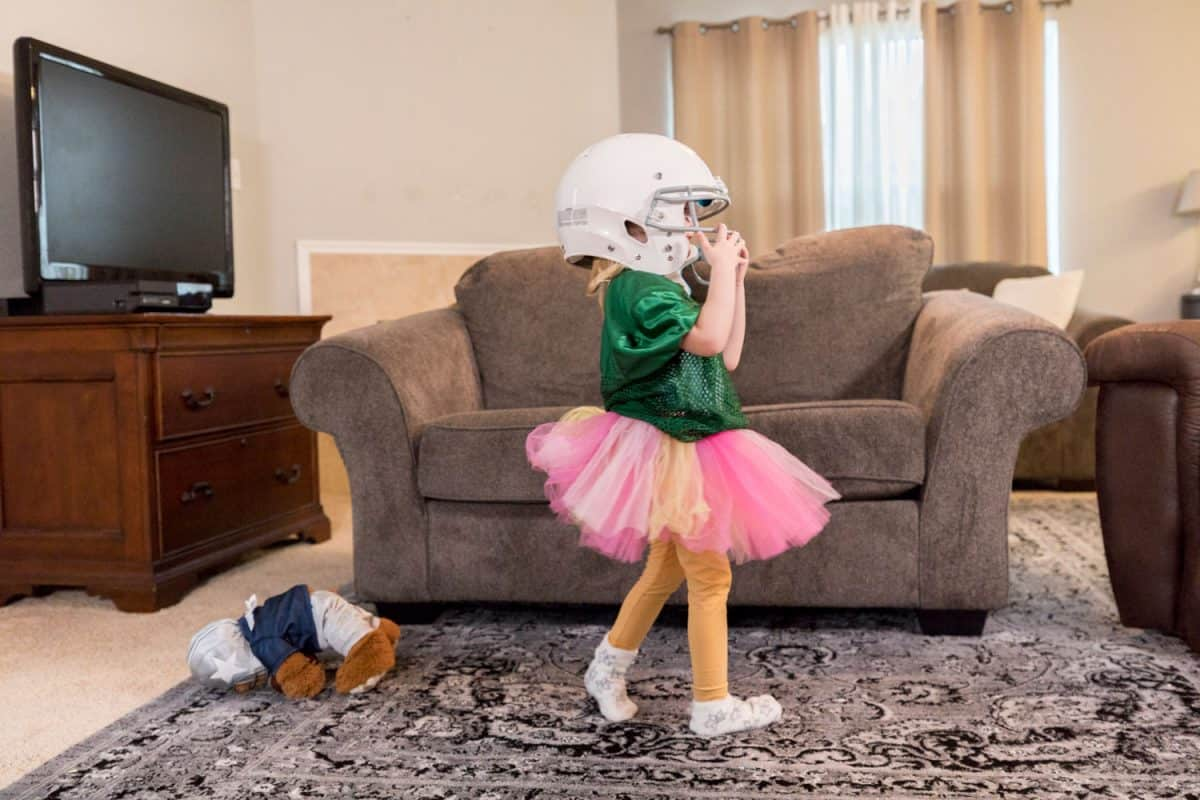 Cute little girl taking off her football helmet after going to the game