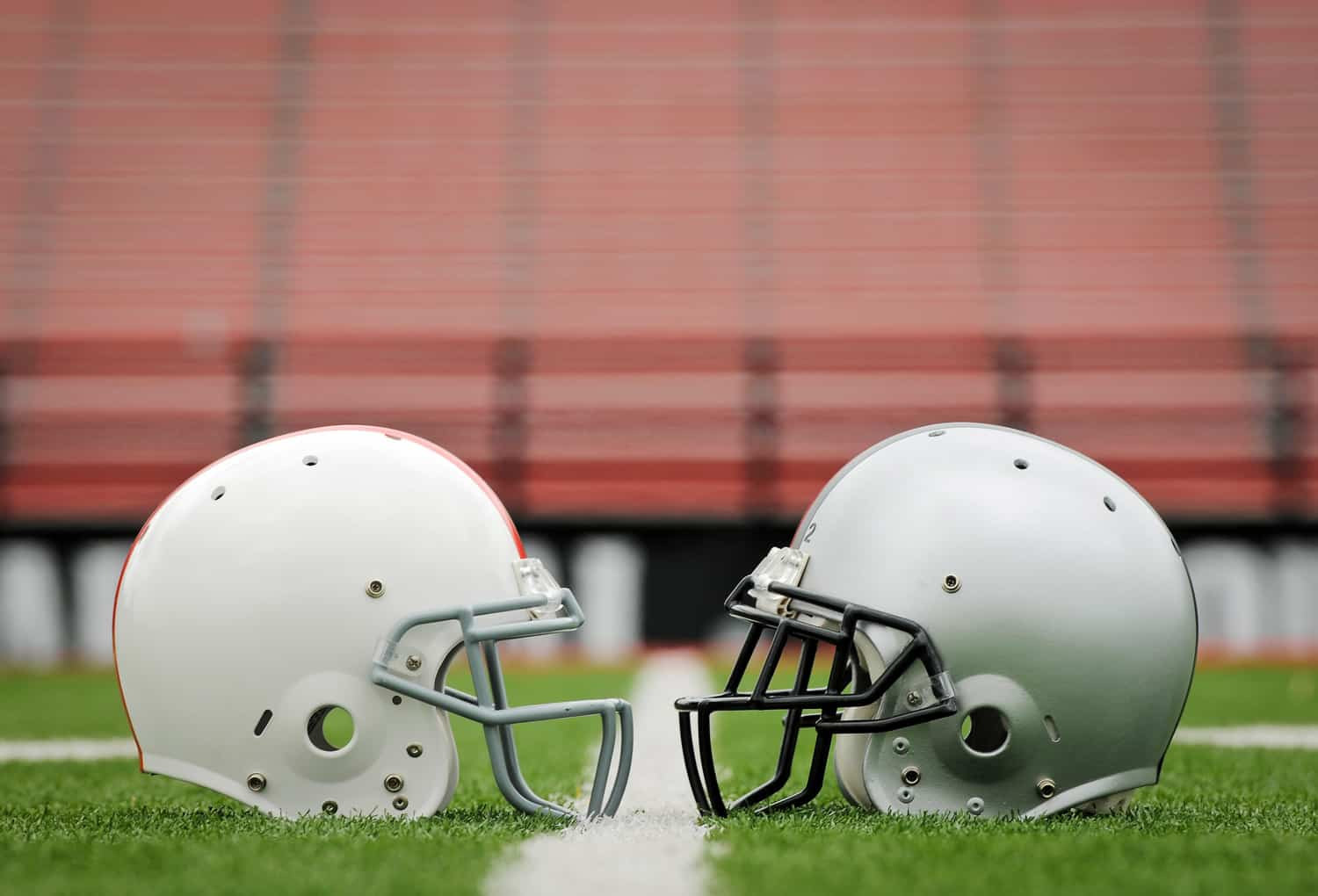 Stock photo of to football helmets sitting face to face on field