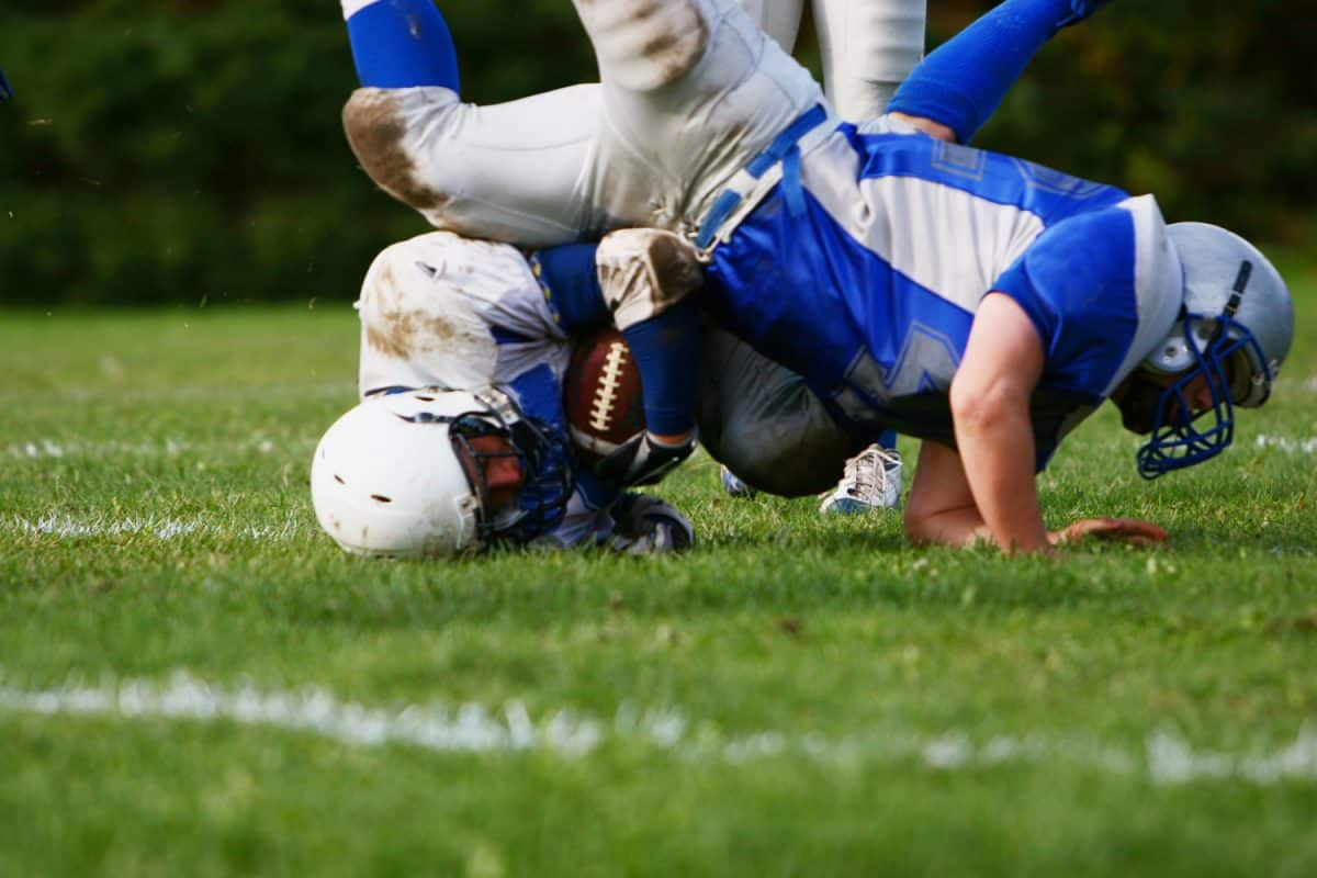 Two football players tackling each other on the ball