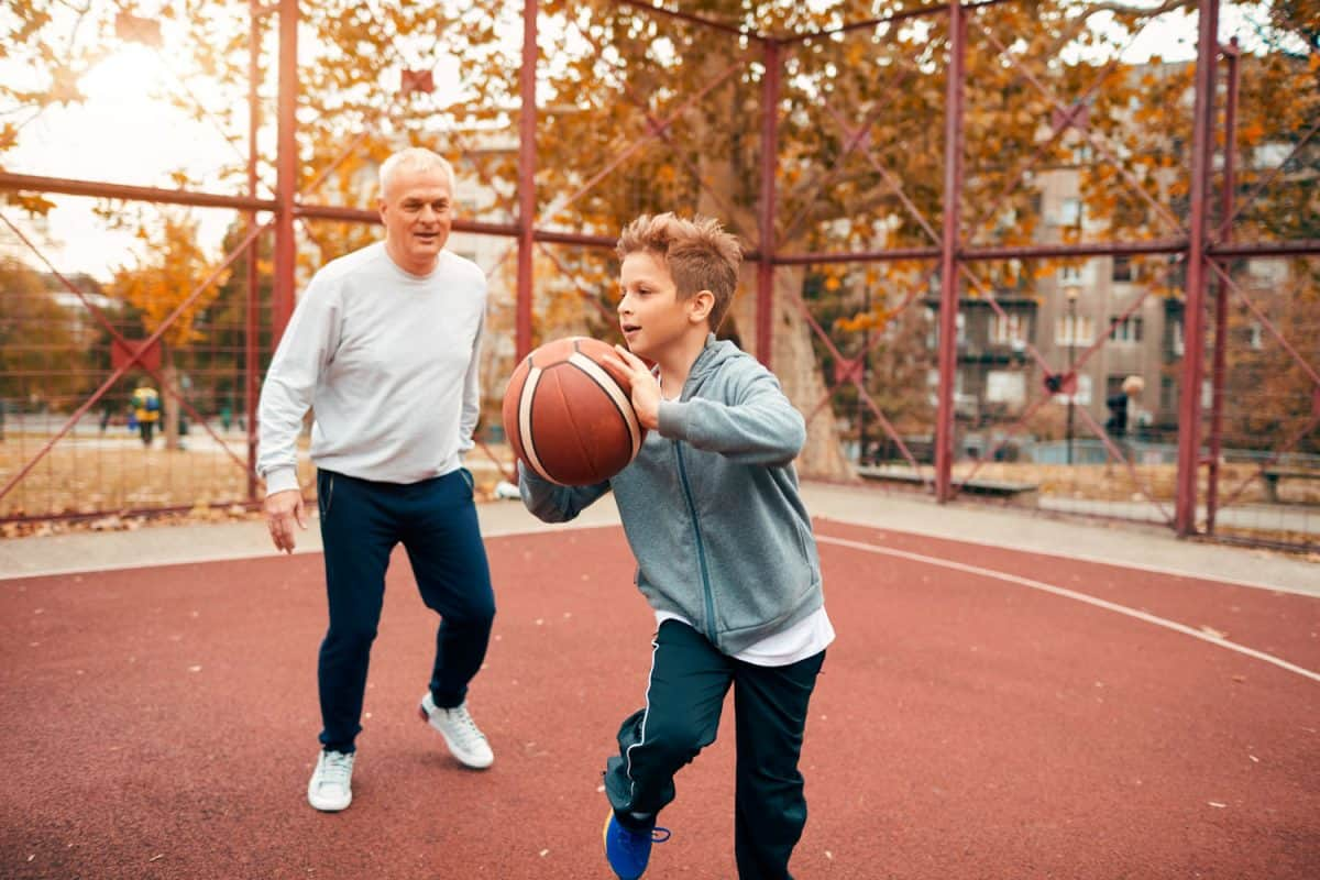 A boy playing basketball with his grandpa