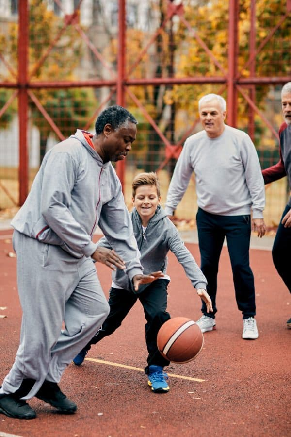 A kid playing basketball with older people